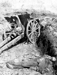 A very grim photo of a deceased British gunner and his artillery piece. No Glory here...