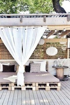 Love the white. The use of pallets. The old wagon wheel thing as a table.