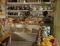 oleson's mercantile image - I love the soft gray here and how it pairs well with golden tones of wood (and the open shelving, willow ware, and cast iron are not bad either! :))