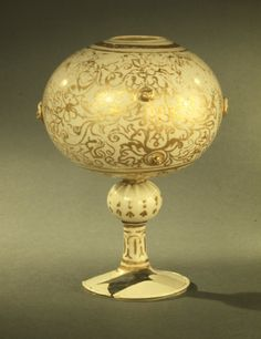 Vessel or wig-stand; opaque white glass; spherical; surface with elaborate gilded decoration, comprising scrolls and mermaids; bosses with masks on body; bulb stem and foot. Italy (Venice), early 16th century.