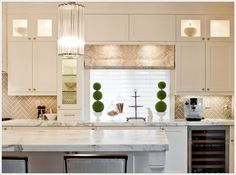 Mhouse Inc.: This backsplash in a tan colour is made through a herring bone design that is looking gorgeous with the kitchen cabinetry and marble counter tops.