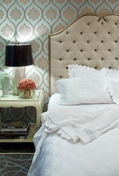 Love this look. Tufted headboard, reading lamp, turquoise patterned wallpaper, and table with a shelf for books. Design by Jamie Herzlinger.