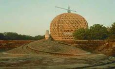 Auroville. Matrimandir. Physically, the Matrimandir is a 100-foot-high elliptical sphere resting on four pillars sunk deep into its foundation. Each pillar represents an aspect of the Divine Mother: Wisdom, Strength, Harmony, Perfection.