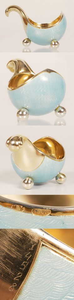 A Faberge Gilded Silver and Pale Blue Guilloche Enamel Kovsh, workmaster Anders Nevalainen, St. Petersburg, circa 1899-1908. The near circular, oval body resting on three gilded silver ball feet, covered with translucent pale blue enamel over engine turned waves.