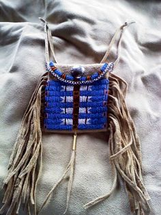 Made by me... I use to do reenactments of the Fur Trade Era.. I made my own clothes and accouterments.. Smoked brain tanned elk hide and glass seed beads.