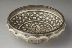 Bowl, Iran. 1260-1350. Mus No. C.53-1955. V This type of ware is known as 'Sultanabad' ware after where it was first found, but was probably made at Kashan. Bowl of fritware, decorated in white slip on a grey engobe outlined in black under a clear glaze. Convex sides, curving in at the lip. The base of the interior decorated with a flying phoenix within a densely populated ground of foliage. The exterior with radiating petals in white outlined in black.