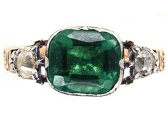An unusual gold and silver Georgian ring with a rectangular green paste in the centre. Emeralds were scarce and very expensive in the early 1800s so paste was often used and this ring is a good example.