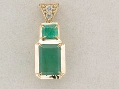 Customers loose emeralds custom mounted in clean yellow gold pendant