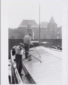 Twee mannen teren het dek van een boot aan de Grote Koppel. Op de achtergrond de spoorbrug en de Koppelpoort.