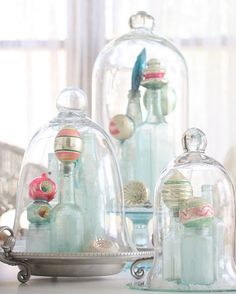 Use old bottles with ornaments on top under a cloche