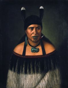 Māori woman wearing a hei-tiki around her neck, pounamu earring and shark tooth earring, and two huia feathers in her hair. She wears a cloak with black fringe border, and has a moko design on her chin.