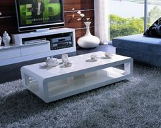 A white lacquered finished coffee table. The coffee table features rounded corners and added storage underneath. - White lacquer coffee table - Modern design - Can be used as a mini TV center as well