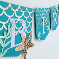 Customize your Mermaid Happy Birthday banner with your littles name. So sweet for your little mermaid princesses party. Each pendant is approximately 4.5x5.5in. Pendants are created in a teal premium heavyweight card stock with a layer of glitter scales. Again a second layer of specialty glitter paper is cut to resemble mermaid scales. A few starfish created with textured gold paper and a coral base, along with lavender and purple seashells add the right amount of whimsy amidst the natural…