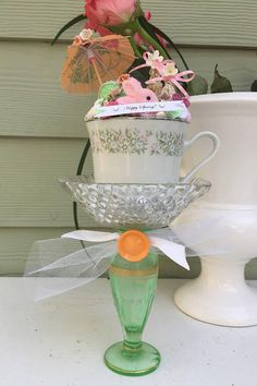 Here comes the Easter bunny! This item features a pink flocked bunny with glittered bottle brush tress nestled into a vintage china teacup. A vintage crystal dish atop a mid century green bud vase. A little treasure to be appreciated for years to come! This handmade and one of a kind