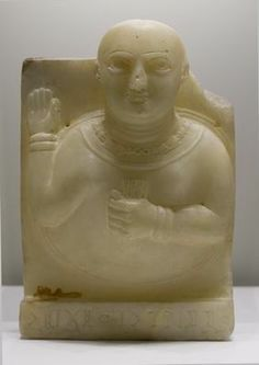 Votive stele of a female bust representing Dhat Hamym, a local sun goddess, inscribed in Qatabanian. Qataban, southern Arabian (Yemen) ca. 2nd century BCE. Alabaster - H: 31.5; W: 13.5 cm Qataban was an ancient Yemeni kingdom whose capital was named Timna. Like most other Old South-Arabian kingdoms it gained great wealth through the trade of frankincense and myrrh, which were spices burned as incense at altars. Qatabanian was a Semitic language spoken in Yemen between 100 BCE and 600 CE,