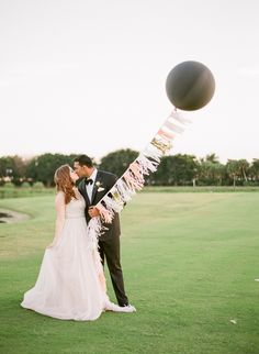 With its expanse of lush green grass and endless blue skies, a posh polo club helps set the stage for a fun-filled celebration that redefines wedding glamour. Fun bride and groom pose with a large balloon and pastel tassel garland Credits: Event Design & Planning-Simply Couture Weddings, Photography-Chelsey Boatwright Photography