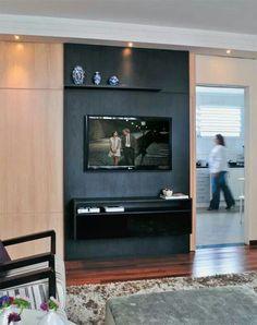 Painel de TV esconde porta da cozinha. Parte clara é uma porta de correr.