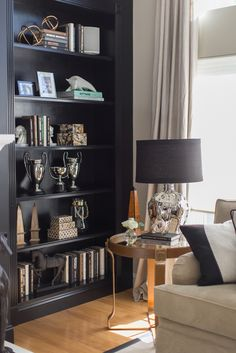 Dark black makes for a bold backdrop for cool bookcase arrangements including vintage silver trophies, masculine accessories and great books.