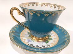 Rich aqua turquoise and touches of gold highlight the large garnet rose. Clarence Bone China of England created this stunning tea cup and saucer. The color is difficult to capture in photos. Picture two with the yellow background is the closest to green blue turquoise paint.