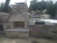Fireplace, pizza oven, and bbq station built from full veneer natural stone by masterpiece masonry ( Jonathan Naddaf )
