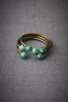 """Sweet Sextet Stacking Rings  $100.00     WRITE A REVIEW  STYLE: 22778310    Six pearl and turquoise posies charmingly mingle on pinky or pointer. Adjustable. From Eric et Lydie. 0.13"""" diameter. Bronze plated brass, enamel, plastic. Handmade in France.    Contact a BHLDN Stylist for style advice, reassurance, second opinions  Color:    color: TURQUOISE    Size:  size:"""
