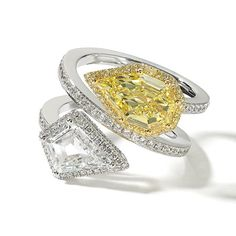 This lovely Victorian era inspired twin stone ring features a magnificent yellow shield cut diamond and a kite shaped white diamond. The motif is completed by diamond framing the twin stones and on the shank. The result – stunning.