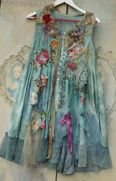 Long feminine floaty cotton vest in shades of aqua, pale blue, turquoise.., with bohemian flair of tattered laces and tulles and intricate details. Lightweight and floaty piece has been hand dyed in uneven shades; reworked with antique laces and antique silk appliques. The bottom edge is