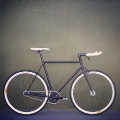 Gray and white fixed gear with bullhorns.