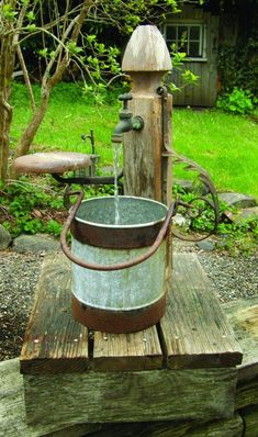 This water feature is the very essence of found object art, made as from a table leg, a rusty bucket and iron remnants, probably from an old buggy.