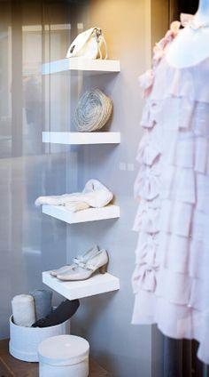 Schuhe und Taschen auf weißen LACK Wandregalen präsentiert