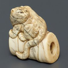 Netsuke, Ivory. Japan, late 19th cent.A very symbolic depiction of a tiger as allegory of supreme power, the bamboo standing for its toughness and unsupressability. Tiger and bamboo are called take ni tora and embody the spirit of the Samurai warrior. The compact and powerful as well as well-rounded crafted netsuke shows tora (tiger, also in the zodiac) sitting on the take with his head looking back. He has black inlaid eyes. Bamboo leaves are carved on the bamboo piece through which the…