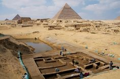 "Pyramids of Giza with newly discovered basin in foreground.remains of mansion that likely held high-ranking officials some 4,500 years ago discovered near Egypt's Giza Pyramids.Bones from young cattle & teeth from leopards suggest residents ate & dressed like royalty.Archaeologists excavating 400meters (1,312feet) south of Sphinx found house & mound with hind limbs of young cattle,seals of ranking officials,inscribed with titles like ""scribe of royal box"" & ""scribe of royal school,""."