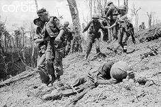 21 May 1969, A Shau Valley, Vietnam --- Injured paratroopers with the 101st Airborne make their way down 'Hamburger Hill' past a wounded colleague with the help of medics, after the hill was taken from North Vietnamese soldiers during fighting in the Vietnam War. --- Image by © Bettmann/CORBIS