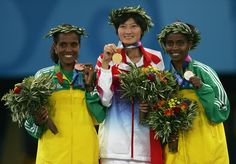 Ejegayehu Dibaba Photos Photos - Gold medalist Huina Xing of China, silver medalist Ejegayehu Dibaba of Ethiopia (L) and bronze medalist Derartu Tulu of Ethiopia celebrate on the podium during the medal ceremony of the women's 10,000 metre event on August 28, 2004 during the Athens 2004 Summer Olympic Games at the Olympic Stadium in the Sports Complex in Athens, Greece. - Olympics Day 15 - Athletics