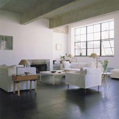 Salon blanc avec plafond en béton brut, murs en béton peint en blanc, le parquet est fait de larges lattes en pin teinté, la cheminée en inoxest  intégrée dans le mur, les tables en bois étuvé sont signées Alvar Aalto.