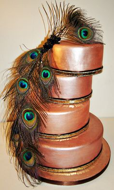 Art Deco Flapper 4 tier cake with cascading peacock feathers. There seems to be a warm glow due to the satin finish in a coppery tone. by MammaJammaCakes.