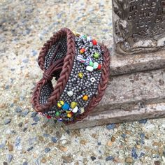 Trade bead and leather cuff African trade beads decorate this beautiful color of gray peyote stitched cuff. Outlined in soft braided leather. IEdesigned Jewelry Bracelets