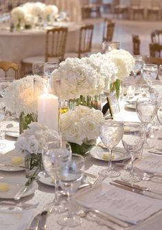 Bright and ambient #Centerpiece ideas with #White flowers and a single #PillarCandle in a cylinder vase.