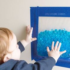 Did you know that babies can safely explore water beads too? I put some in a large ziplock bag and taped it to the wall with painters tape. My little guy was able to explore them safely without me worrying about him trying to pop them in his mouth for a little taste test! He's working on standing unassisted at the moment, so I taped it at a height that required him to stand to explore. This would be great for babies learning to sit upright too or even babies during tummy time when taped to…