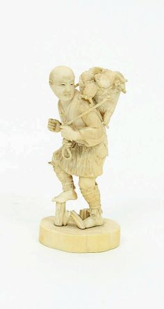 A Japanese ivory okimono, Meiji period, depicting a man carrying a basket of tortoises, 14cm high