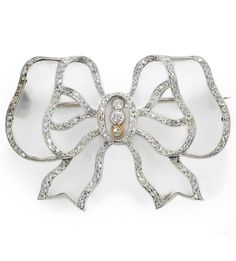 An Edwardian rock crystal and diamond brooch, circa 1910. Designed as a bow, the carved rock crystal ribbon mounted within millegrain-set rose-cut diamond borders, 4.0cm. #Edwardian #brooch