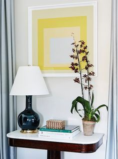 A vibrant yellow modern art print adds a dose of color and modern style to this timeless mahogany pedestal table in the entry hall.
