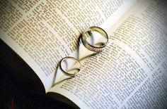 Wedding rings create heart over Love poem in bible