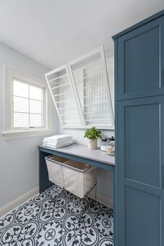 Side-by-side pull out drying racks are mounted in this well designed blue powder room and are positioned over a white quartz countertop fitted over vintage laundry carts placed on black and white quatrefoil tiles. Blue Laundry Rooms, Laundry Room Design, Mud Rooms, Vintage Laundry Rooms, Boudoir Bleu, Blue Powder Rooms, Drying Rack Laundry, Laundry Cart, Laundry Closet