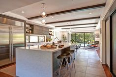 The sleek, contemporary island featured in this open plan kitchen boasts a marble waterfall countertop with plenty of space to eat and prepare food.