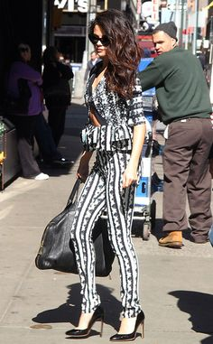 For an appearance on Good Morning America in New York, the brunette beauty dons a Peter Pilotto Lara top featuring a cutout detail and ruffled peplum with matching pants. She accessories her printed attire with a black oversize handbag and Rubert Sanderson Troy pumps.
