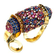 ღ♥♥ღ John Rubel, A Retro Ruby, Sapphire and Diamond Rouleau Bracelet, designed as a central cylinder set with circular-cut rubies, sapphires and diamonds, with similar bombé terminals, to the bifurcated swivelling gold sides, mounted in gold, inner diameter measures approximately 5.8cm, signed John Rubel Co., circa 1945.