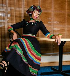 Clipkulture - The Best Wedding Planner for Traditional Wedding Decor! Zandi in black flare umbhaco dress with colourful embroidery patterns. Crowned with colourful designed Doek and earrings. Outfit by Scripture. South African Dresses, Latest African Fashion Dresses, African Print Fashion, Africa Fashion, African Attire, African Wear, African Outfits, African Lace, African Prints