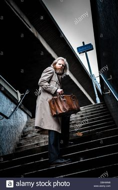 Bearded man in suit and overcoat holding an old leather briefcase walking up steps out of