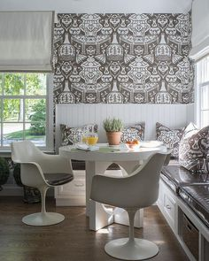 White and brown dining nook is filled with a corner L shaped banquette fitted with drawers and topped with brown vinyl cushions and pillows in The Vase Fabric.